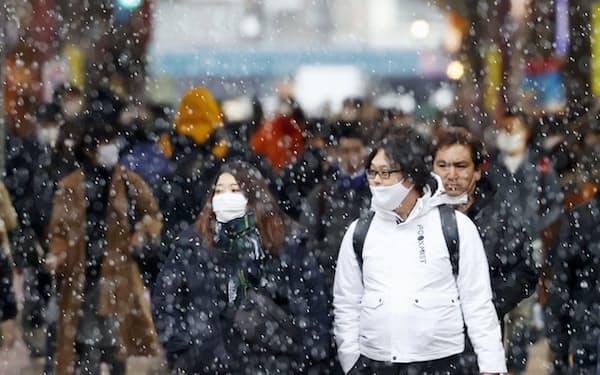 雪が降る中、札幌市の商店街をマスク姿で歩く人たち                                                       (9日)
