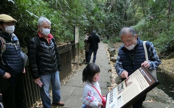 タビカのホスト役として等々力渓谷を案内する小池さん(右)は子供にも丁寧に説明
