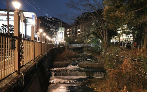 漱石が滞在した旅館跡には美術館や会員制ホテルが立つ。温泉街を流れる川面に街灯の明かりが映る=竹邨章撮影