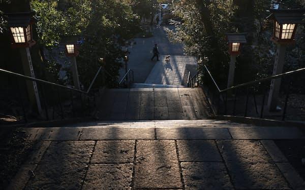 夕暮れ時の谷保天満宮。境内の階段を西日が照らす=三村幸作撮影