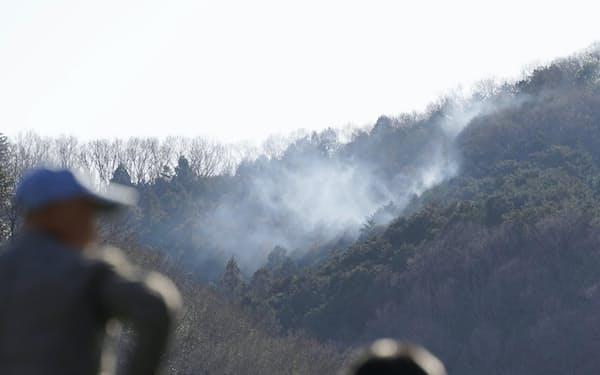 栃木県足利市の山林火災で、山から上る煙を見つめる人々(2月27日)