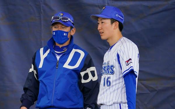 三浦大輔監督(左)と話す大貫。今年のキャンプでは速いカーブの習得に取り組んだ=球団提供
