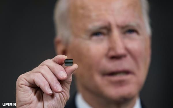 半導体チップを掲げるバイデン米大統領(2月24日、ワシントン)=UPI共同