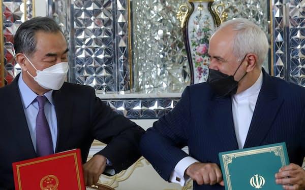 中国の王毅外相(左)とイランのザリフ外相は3月27日に、イランと経済や安全保障を巡る25年間の協定に署名した=ロイタ-