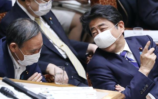 参院予算委で菅官房長官(左)と言葉を交わす安倍首相(2020年6月、肩書は当時)