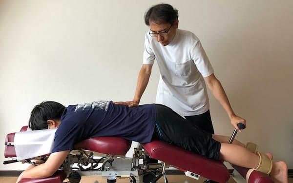 腰をくの字に曲げ、脊柱管を広げて痛みを和らげる(東京都中央区の竹谷内医院)
