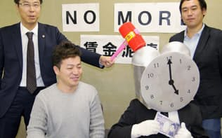 ポーズを取る「NO MORE 賃金泥棒」プロジェクト呼び掛け人の佐々木弁護士(左)ら(東京都内)