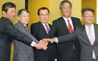 4カ月のスピード交渉で統合に基本合意した(2015年12月の記者会見に出席した内田JXHD社長=左から2人目、武藤東燃ゼネ社長=同4人目、東京都内)