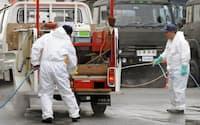 役場の駐車場入り口で、口蹄疫対策の消毒を受ける作業車(20日午後、宮崎県川南町)=共同