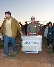 小惑星探査機「はやぶさ」のカプセルが入ったコンテナを運ぶJAXAの研究者ら(14日、豪・ウーメラ付近)=共同