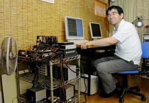 円周率を5兆けたまで計算した近藤茂さん。左が自作のパソコンで、むき出しの部品を扇風機で冷やし続けた(11日、長野県飯田市)=共同