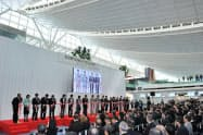 羽田空港の新国際線ターミナルビルで開かれた記念式典でテープカットする出席者(16日午前)