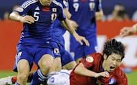 日本-韓国 後半、長友(左)と競り合い倒れる韓国の朴智星。中央は本田圭(25日、ドーハ)=共同