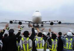 最後のフライトを終えた日航ジャンボ機を、職員らが出迎えた(1日午後、成田空港)