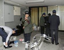強盗傷害事件があった警備会社「日月警備保障立川営業所」を調べる捜査員(12日午後、東京都立川市)=共同