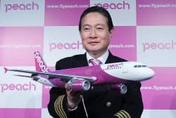 ブランド名「Peach」をデザインした機体の模型を手にするエーアンドエフ・アビエーションの井上慎一CEO(24日午前、大阪市北区)