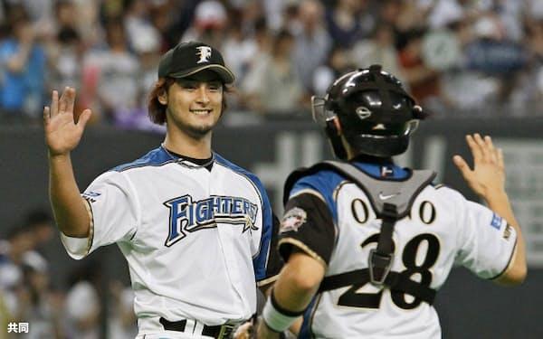 3試合連続完封で8勝目を挙げ、笑顔で捕手大野とタッチを交わす日本ハム・ダルビッシュ(8日、札幌ドーム)=共同