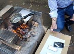 TESニューエナジーが製品化した「発電鍋」。鍋の柄から伸びたコードを携帯に接続して充電する