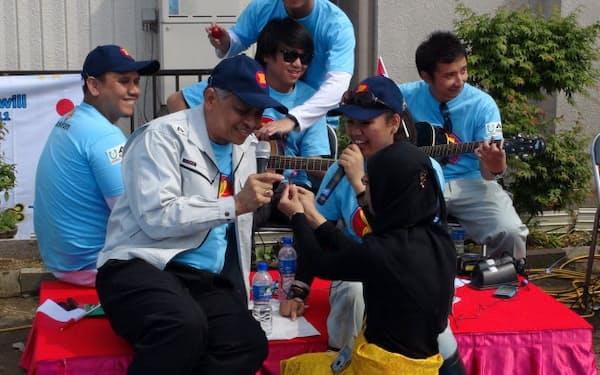 キャラバンの若者と歌うASEAN事務総長のスリン(前列左)=4日、石巻市
