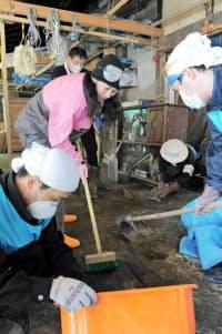 民家の倉庫にたまった泥をかき出す、県外からきたボランティア(2011年5月3日、宮城県七ケ浜町)