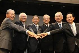 記者会見後、手を重ねるトヨタ自動車の豊田章男社長(左から3人目)ら(13日午後、名古屋市中村区)