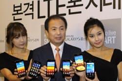 高速携帯電話サービス「LTE」対応の新型スマホを手にする申無線事業部長(26日、ソウル市内)