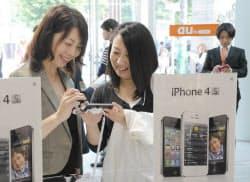 KDDIのショールームで「iPhone4S」を手に取る人たち(14日午前、東京都渋谷区)