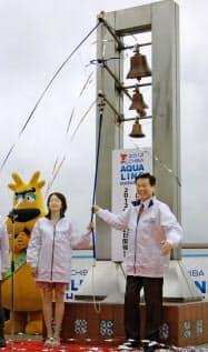 「ちばアクアラインマラソン」1年前イベントで、マラソンランナーの千葉真子さん=左=と鐘を鳴らす千葉県の森田健作知事(21日、千葉県木更津市の海ほたる)=共同