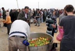 25日、トルコ東部エルジシュで、食料配給を求めて整然と列をつくる人たち=共同