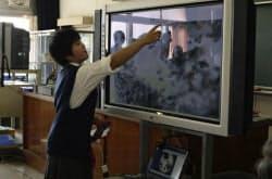 iPad2でまとめたリポートを教室内の電子黒板に映しプレゼンテーションする生徒