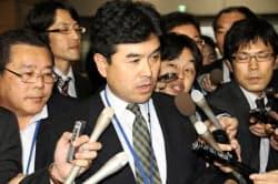 防衛省に到着し、記者に囲まれる田中聡沖縄防衛局長(29日午後)=共同