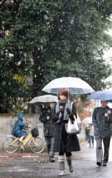 雪の中を歩く人たち(9日午前、東京都武蔵野市)