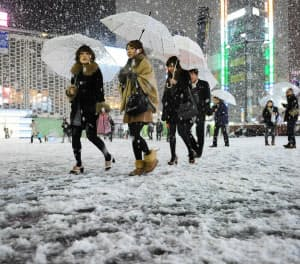 積もり始めた雪に、家路を急ぐ人たち(23日夜、東京・新橋)