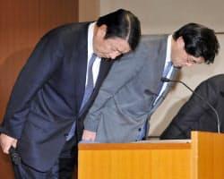 記者会見で頭を下げるNTTドコモの山田社長(左)ら(27日午後、東京・大手町)