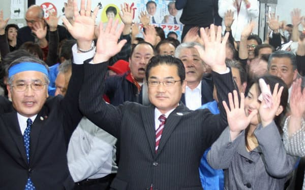 沖縄県宜野湾市長選で当選し、万歳する佐喜真淳氏(12日夜)