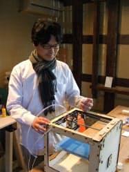 3次元印刷機を操作する田中准教授(鎌倉市のファブラボ鎌倉)