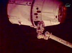25日、国際宇宙ステーションのロボットアームにつかまれた無人宇宙船ドラゴン=NASA提供・共同