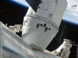 国際宇宙ステーション(下)とドッキングした無人宇宙船ドラゴン=NASA提供・共同