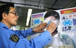オウム真理教元信者の高橋克也容疑者の等身大パネルに、「逮捕」と書かれたシールを貼る蒲田署の副署長(15日、警視庁蒲田署)=共同