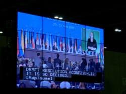 22日、リオ+20で成果文書を採択して拍手する各国からの参加者(リオデジャネイロのメディアセンターの大画面)