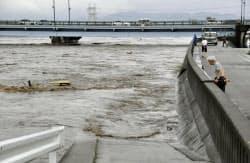 大雨の影響で増水した熊本市内を流れる白川(12日午前8時ごろ)=共同