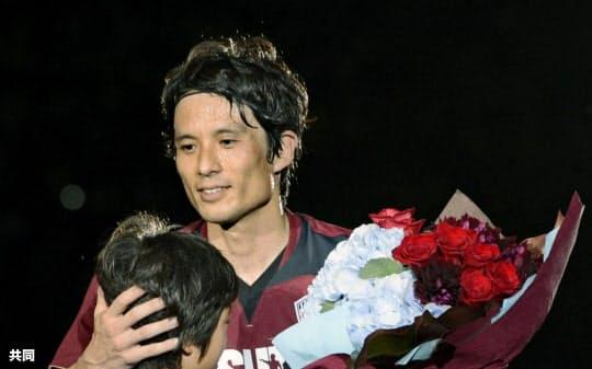 引退試合を終え、長男の恒凛君から花束を手渡されるサッカーの元日本代表主将、宮本恒靖氏(16日、ホームズスタジアム神戸)=共同