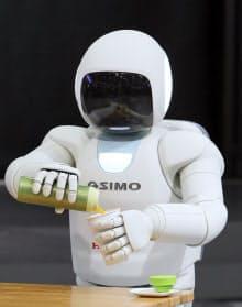 コップにジュースを注ぐ新型の二足歩行ロボット「ASIMO(アシモ)」(21日、東京都港区のホンダ本社)