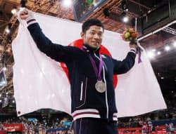 柔道男子60キロ級で銀メダルを獲得し、日の丸を広げる平岡拓晃=写真 佐光恭明