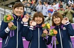 女子団体で銅メダルを獲得し、笑顔の(左から)早川漣、蟹江美貴、川中香緒里(29日、ローズ・クリケット場)=共同