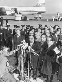 ワシントンで改定安保条約に調印し、帰国した羽田空港で声明を読み上げる岸信介首相。後列左が椎名悦三郎官房長官=毎日新聞社提供