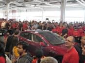 新型車出荷を祝うテスラの従業員(6月、米カリフォルニア州フリーモント市)