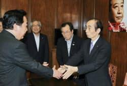 消費増税法が成立し、民主党の輿石幹事長と握手する野田首相(10日、国会内)