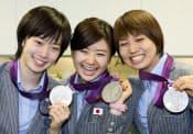 卓球女子団体で獲得した銀メダルを手に笑顔を見せる(左から)石川、福原、平野の3選手(10日午後、成田空港)=共同