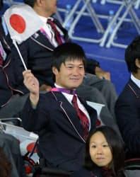 開会式で、日の丸を振って入場行進する車いすテニスの国枝慎吾(29日、五輪スタジアム)=共同